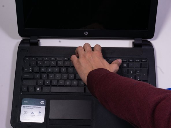 Once a large enough portion of the laptop is lifted up, use your hand to finish separating the keyboard from the laptop
