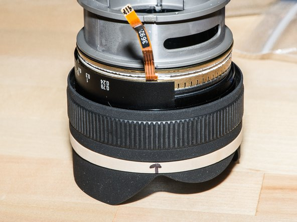 Put a tab of masking tape, or an elastic band, on the lens hood (not the focus ring). Mark the location of the ribbon cable. This will save you much grief during reassembly.