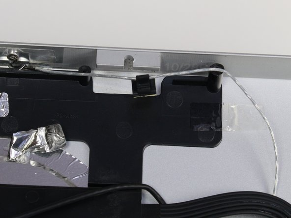 The webcam is held in place with a plastic clip that has foam adhesive stuck to the casing.