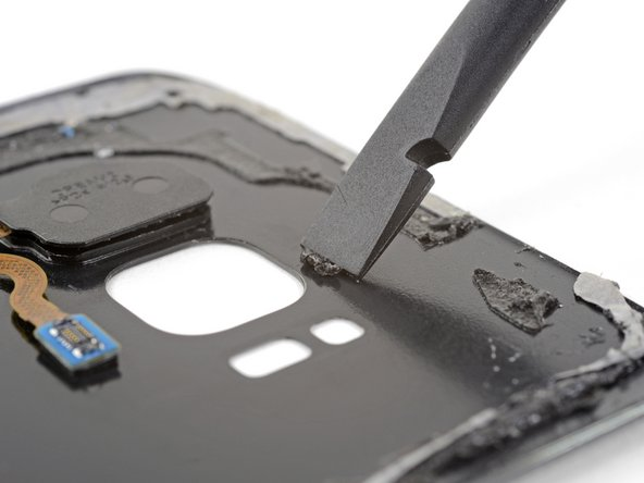 Use a spudger to scrape away any adhesive where the camera bezel adheres to the rear glass.