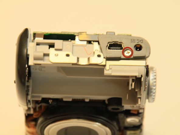 Remove the two fine thread screws on the top of the keypad.  Then remove the one coarse thread screw holding the plastic piece in place on the side of the camera.  Remove the plastic piece.
