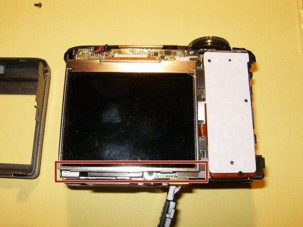 Lift the LCD out of its frame, but do not fully detach it yet. It is still attached to the camera by two ribbon cables.