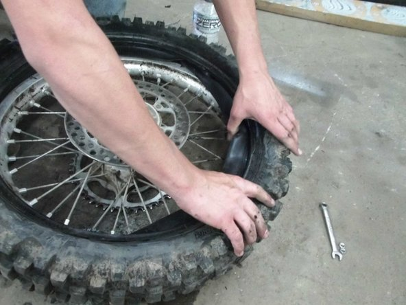 Put the new tube in the tire. put the valve stem through the hole in the rim then put one of the nuts on it.( not the bead lock.) Add a little bit of air to the tube.(the less you use the better off you are.)