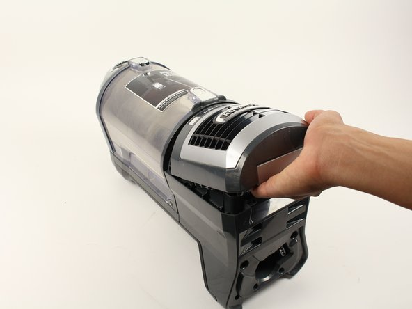 Pull the silver release latch and lift away from the body of the vacuum from the bottom.