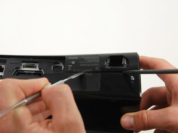 Insert the flat edge of a metal spudger between the left and right cases where the warranty sticker used to be.