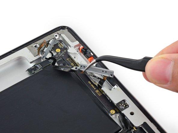 Repliez la nappe vers l'intérieur de la coque arrière, mais n'essayez pas de l'enlever, car elle est toujours connectée à la carte des composants supérieurs.
