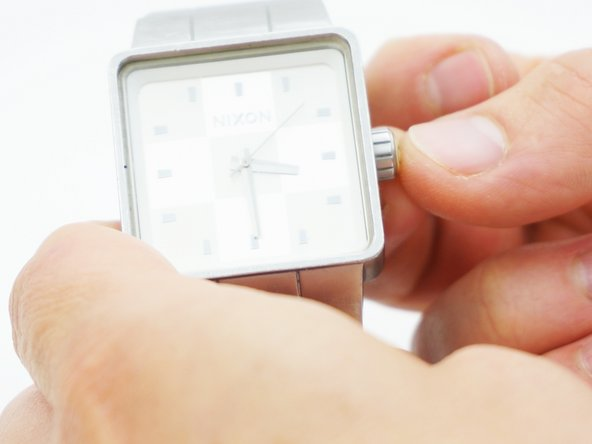 Pull the crown away from the watch and then turn the knob to set the time.