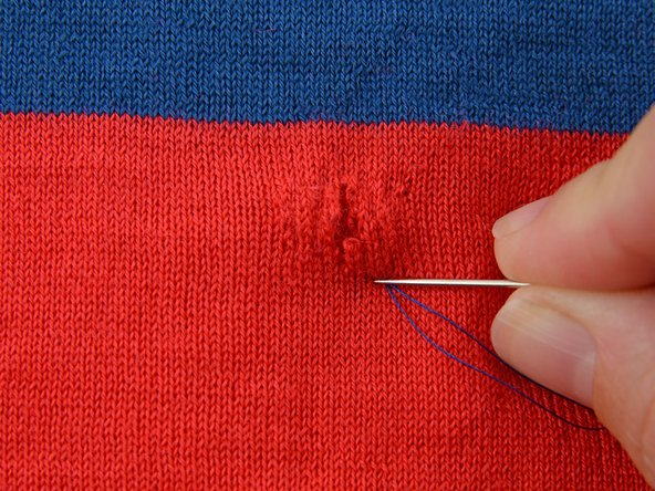 Take a single straight stitch going into a single layer of fabric and coming back up one row of the knit closer to the hole.