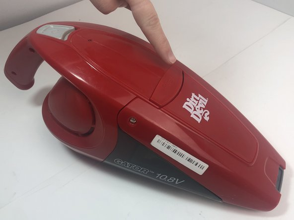 Press the button on the middle of the vacuum by pushing down on it and pulling the device apart.