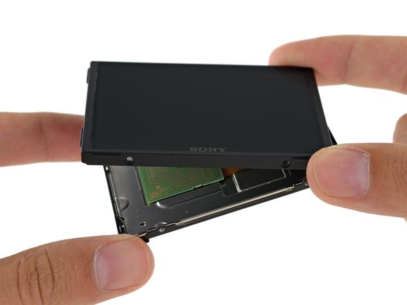 The rear LCD panel is connected by a thin ribbon cable that disappears into the back of the camera body. We'll probably have to deal with that before we can crack open this camera...