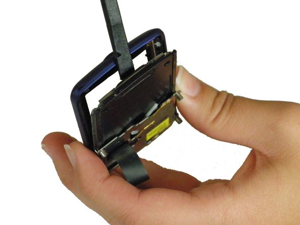 Image 1/3: Use the spudger to pry the ribbon cable away from its clip on the LCD unit.