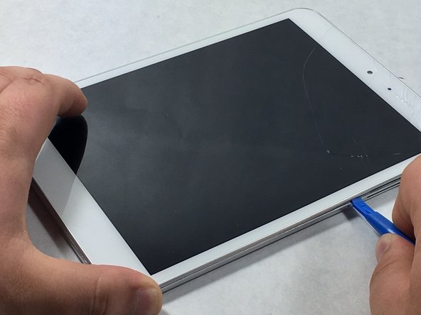 Image 1/1: Use a plastic opening tool to remove the metal backing of the tablet.