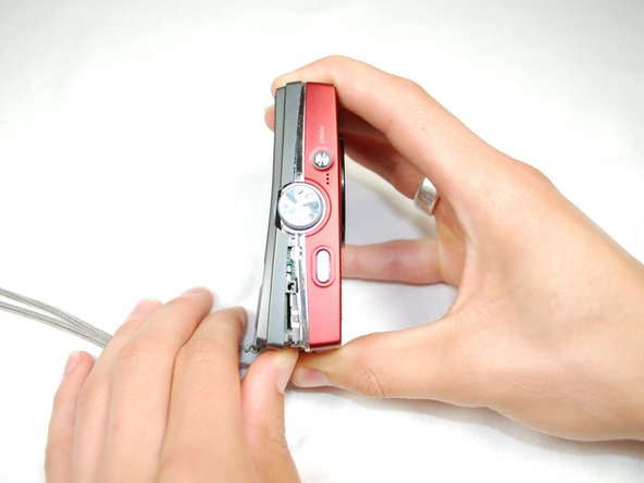 Slide your fingernail or a plastic spudger in the groove from the bottom to the top of the right side of the camera.