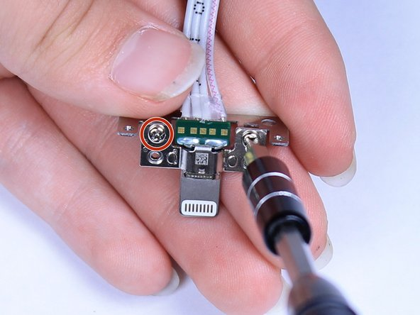 Using a Phillips #0 screwdriver, unscrew the two 3mm Phillips screws from the metal frame around the lightning cable.