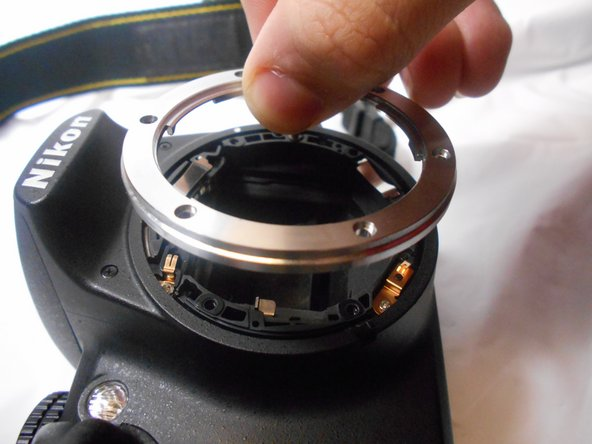 Image 2/2: The small metal plates marked in the image are not fastened and may displace if the camera if tipped or bumped. Be sure these are properly in place before reassembly.