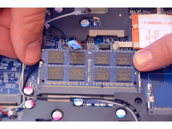 Locate and squeeze the tension springs that secure the memory module apart.