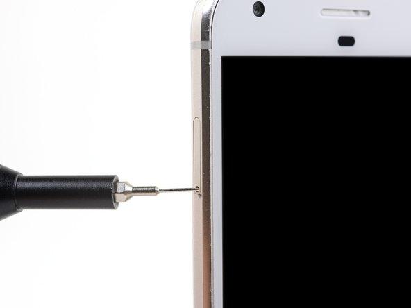 Setze ein SIM Auswurfwerkzeug, einen SIM Auswurfbit oder eine aufgebogene Büroklammer in das kleine Loch oben in der linken Seitenkante des Smartphones ein.