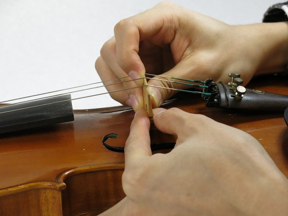 After tightening all four strings, play a little to test the string placement. If the distance between the strings is not comfortable for performance (as noted in step 4), repeat step 2-6 and adjust the distance between the strings on the bridge again to find the proper distance.