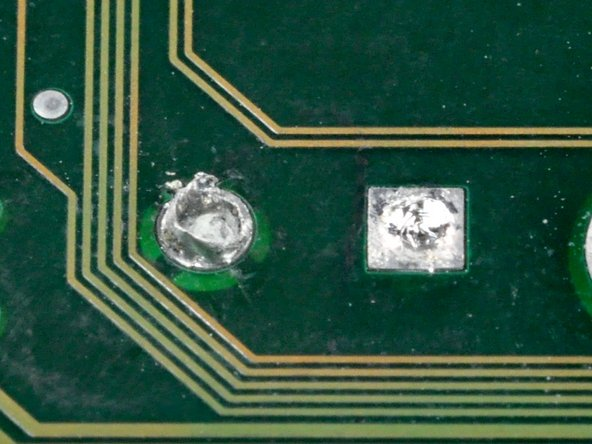 Image 1/1: A capacitor was already removed from the two solder pads. Each pad was heated while the capacitor was pulled away from the board.