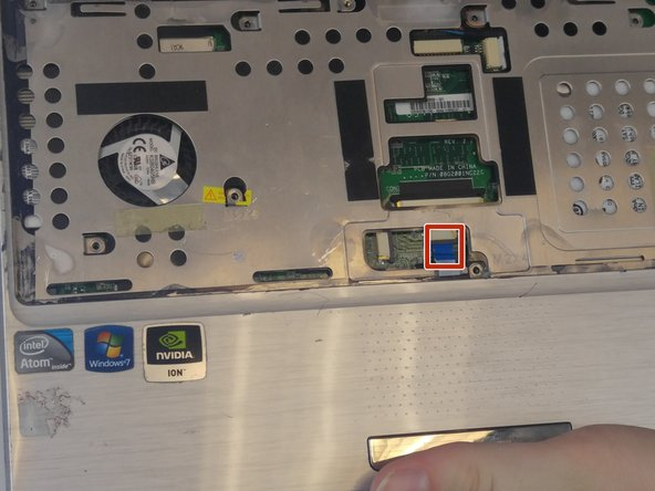 Flip up the retaining flap on the ZIF connector. Then, pull the blue tab for the touchpad connector before removing the cover plate completely.