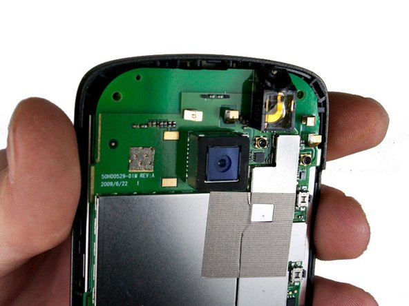 Locate the four metal tabs on the top and bottom of the camera holding the camera enclosure to the motherboard.