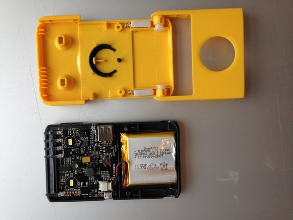 Now you see all the components in the Waka Waka. The battery is attached to the case with tape, so you have to use force to pull it off.