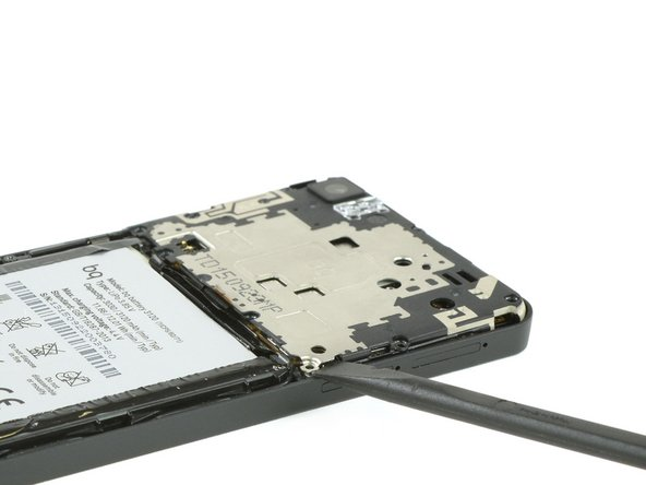 Insert the flat side of a spudger between the mainboard shield and the frame of the phone.