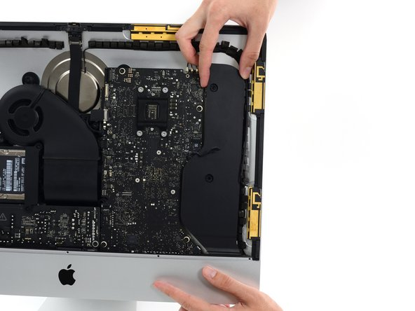 Image 1/3: Lift the right speaker straight up and remove it from the iMac. This may take some force, both hands and rocking the speaker right and left to get it out.