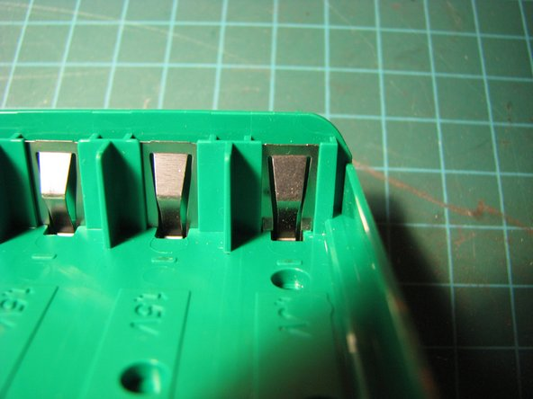 Pull the right side of the battery compartment away from the top case. The left side will be held in place by the battery clip.