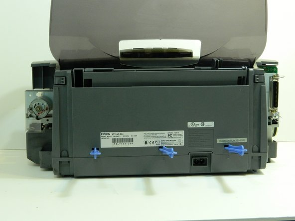 Turn the printer around so the front is facing away.  Use three wide-tip blue plastic opening tools and place them inside the notches on the back panel of the printer.