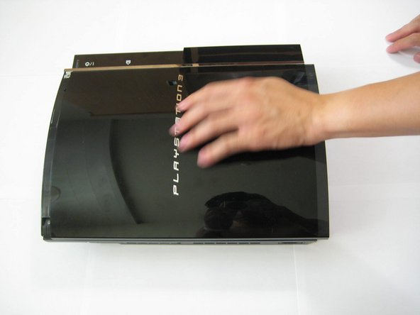 Place your palm on the PlayStation 3 logo and slide the plastic front cover towards you and off of the outer plastic shell. Set it aside.