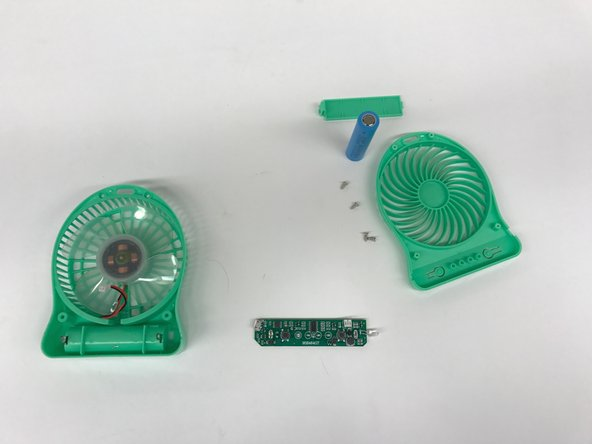 The PCB is disconnected from the DC motor and desoldered from the rest of the fan structure and laid to rest next to the remaining fan components.