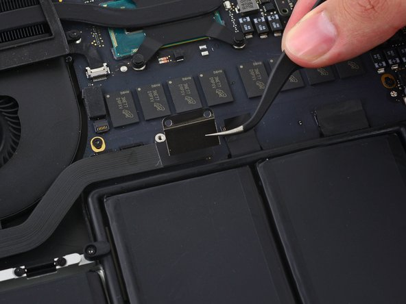 Grasp the I/O board cable bracket with a pair of tweezers and remove it from the MacBook.