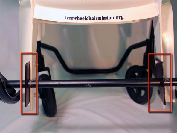 Turn the chair around and locate the two base plates that hold the axle to the back of the chair.