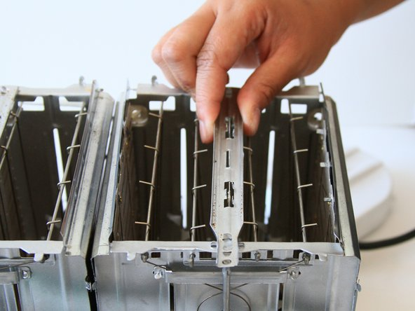 Image 2/3: Pull the metal spacer upwards to release from the toaster.