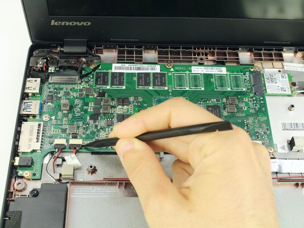 Use the spudger to coax the sliding speaker cables toward you, out of the motherboard attachments.