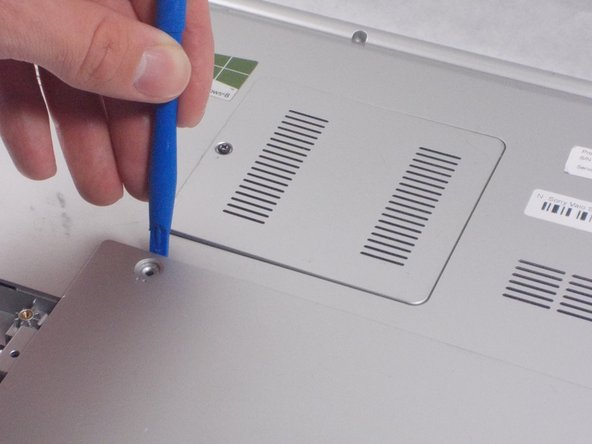 Push down on the plastic opening tool until the battery lifts from the back of the laptop.