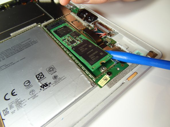 Use a blue plastic opening tool or spudger to lift the SSD drive slightly and grasp it with your fingers. Pull the drive down towards yourself to remove it from the device.