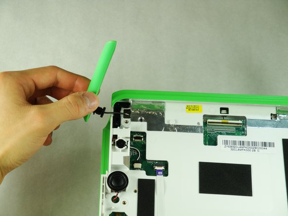 On the front side of the laptop, carefully pull the wire through the hole and out.