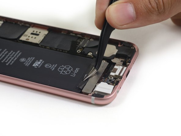 Use tweezers to peel up the edges of the two adhesive strips at the bottom of the battery.
