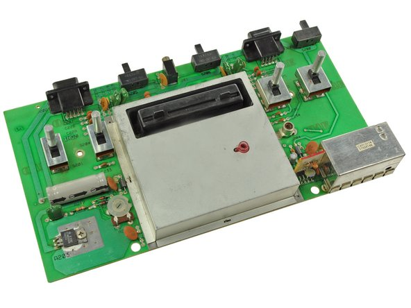 The motherboard of the 2600 is dominated by an ominous metal box, likely the EMI shield covering the ICs.