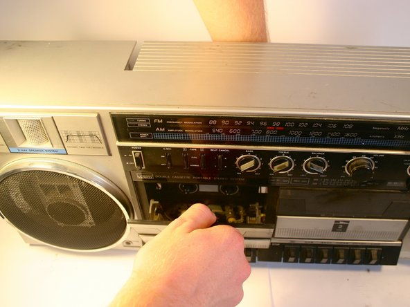 Image 1/3: Gripping the cassette player from the back, lift upwards on the door to unclip it from the bar around which it rotates. This may take some effort.