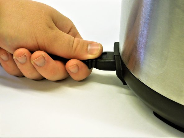 Grasp the power cord input connector firmly with forefinger and thumb.