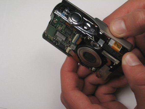Take hold of the inside of the camera, and gently pull away from the back casing.