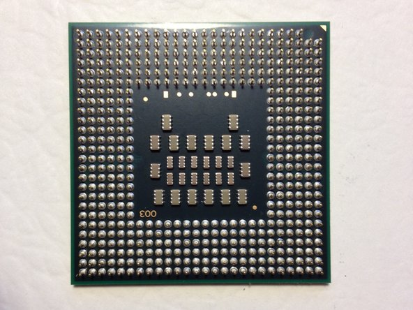 Insert your new CPU into the ZIF socket.  Note that two pins are missing from one corner of the grid.  Match that corner with the corner of the socket that is missing the corresponding holes.  Drop the chip in; it should go in without effort.  Rotate the screw on the socket 180 degrees clockwise to lock the new CPU in place.