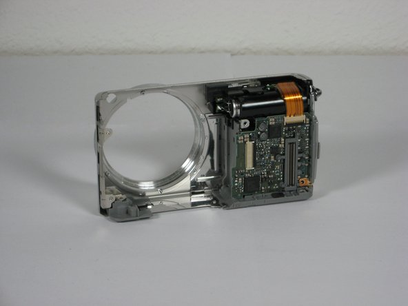 The ribbons on the left and bottom of the assembly simply rest on the camera housing.