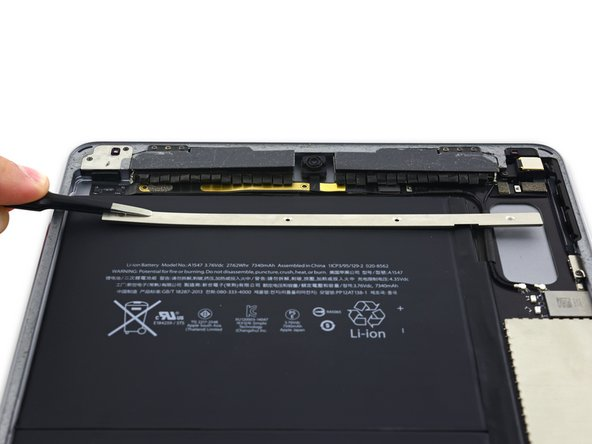 Image 3/3: Slide the upper component cable bracket out from under the protective flaps and remove it from the iPad.