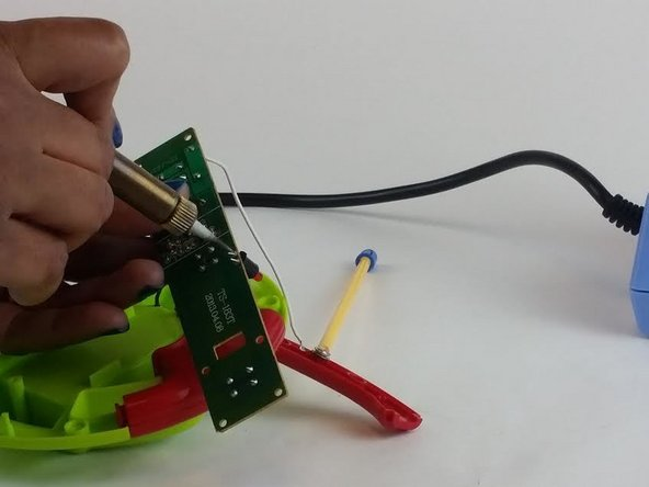 Image 1/1: While the solder is liquid, lightly pull on the LED to remove it from the motherboard.