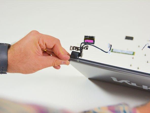 Image 2/3: Orten Sie die Schraubenabdeckung des rechten Scharniergelenkes.