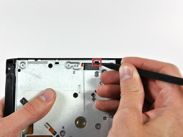 Use the sharp end of a spudger to push the optical drive bracket tabs out of their slots on the bottom of the optical drive.